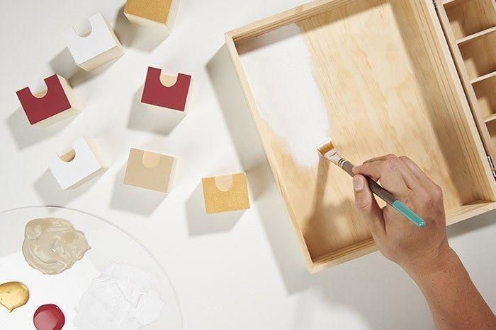 1. Peindre le fond du casier « vitrine » et 7 façades de tiroirs en blanc, 6 en rouge brique, 4 en doré et 3 en gris taupe. Conseil : Pour créer un coloris gris taupe, mélanger 2/3 de peinture ficelle, 1/3 de doré et ajouter un peu de gris souris. Utiliser du ruban de masquage pour éviter les débords de peinture.