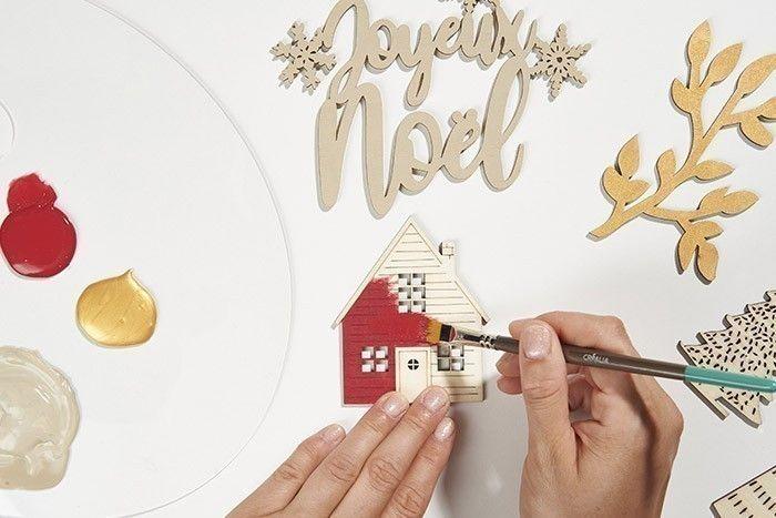2. Peindre les accessoires décoratifs : les végétaux en doré et le mot Joyeux Noël en gris taupe. Peindre la façade de la maison en rouge brique, le cadrant de la porte en gris taupe et le toit en doré.