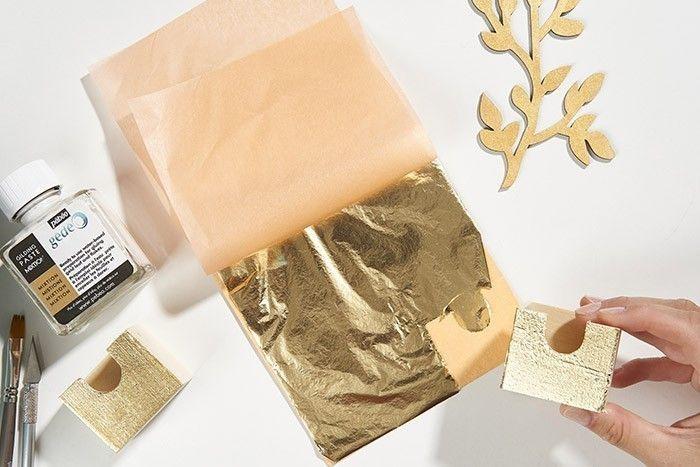 4. Pour faciliter le travail de la dorure en aplat, poser un premier tiroir doré encollé de mixtion sur la feuille d'or. Entailler légèrement la feuille à dorer à l'aide d'un cutter de précision le long des contours du tiroir puis le retirer délicatement.