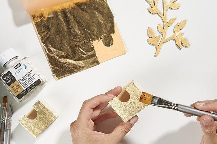 5. Brosser la surface à l'aide d'un pinceau sec. Conseil : si la feuille à dorer n'a pas recouvert toute la surface du tiroir, enduire les parties manquantes de mixtion, laisser sécher et poser avec le doigt un copeau de feuille à dorer.