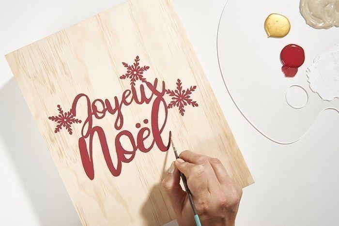 8. Télécharger, imprimer et reporter le contour du gabarit du mot Joyeux Noël sur le papier calque à l'aide d'un crayon à papier. Positionner le motif reporté face contre la couverture du livre en bois et tracer à nouveau le motif qui se décalque sur le support. Peindre minutieusement en rouge tout le mot. Laisser sécher.