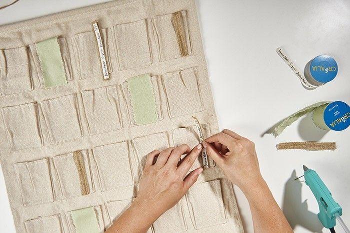 ETAPE 2/8 Coller le ruban lin à la verticale à différents endroits du calendrier de l'Avent à l'aide du pistolet à colle. Superposer le ruban jute et le ruban de Noël sur certaines pochettes. Varier les compositions.