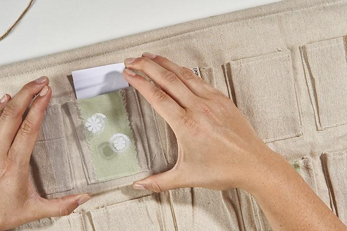 ETAPE 5/8 Appliquer le tampon sur une pochette ou le ruban lin. Répéter ces étapes avec d'autres tampons à différents endroits. Laisser sécher. Conseil : Si vous souhaitez appliquer le même motif plusieurs fois, enduire de nouveau le tampon de peinture blanche.