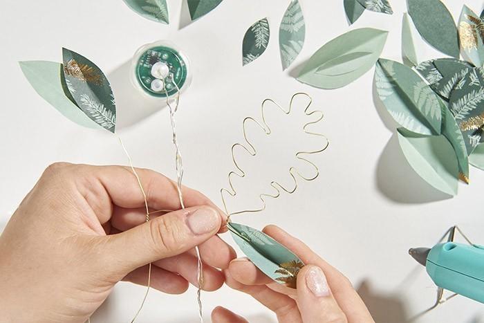 ETAPE 4/9 Choisir les papiers verts du set de papiers origami et les plier plusieurs fois sur eux-mêmes.