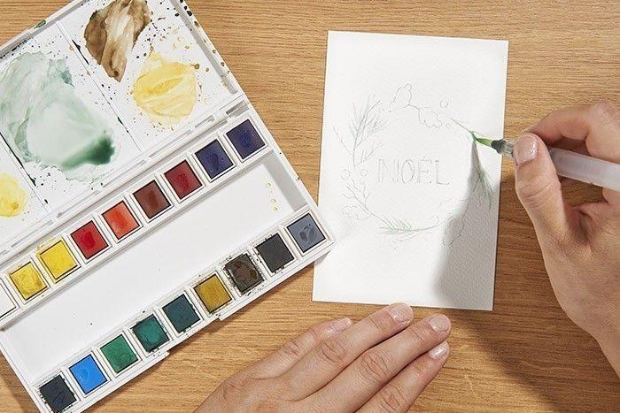 ETAPE 2/9 CRÉATION DE CARTES DE NOËL Mélanger l'aquarelle bleu de prusse, vert viridian et ombre brûlée avec beaucoup d'eau sur la palette et peindre les premières branches de sapin. Laisser sécher.