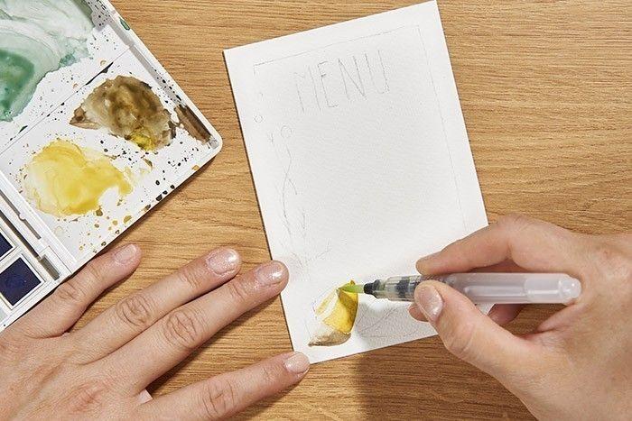 ETAPE 7/9 CRÉATION DE CARTES MENU Pour peindre le gland de l'autre carte Menu, faire un dégradé avec le mélange ocre jaune et jaune gambodge et diluer la couleur avec le pinceau à réservoir d'eau. Laisser sécher. Réaliser un dégradé pour le chapeau du gland avec l'ombre brûlée. Conseil : Laisser le blanc du papier pour apporter la lumière entre vos deux dégradés.