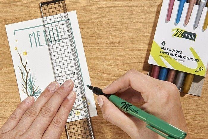 ETAPE 8/9 Tracer le mot Menu et l'encadré avec le marqueur pinceau métallique vert en vous aidant d'une règle. Réaliser autant de cartes que d'invités et inscrire au dos votre menu avec le fineliner.