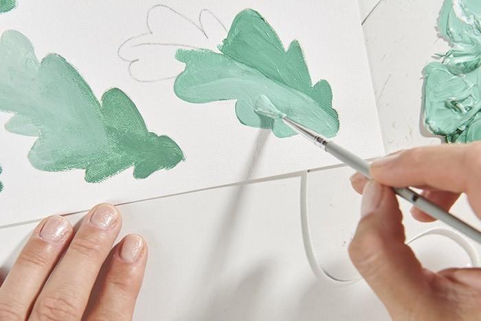 ETAPE 2/9 Peindre les feuilles en faisant des dégradés. Réaliser un mélange de vert foncé, d'or et de gris, le décliner en plusieurs nuances de verts en ajoutant du blanc. Une fois sèches, faire les nervures au pinceau fin avec un vert clair.