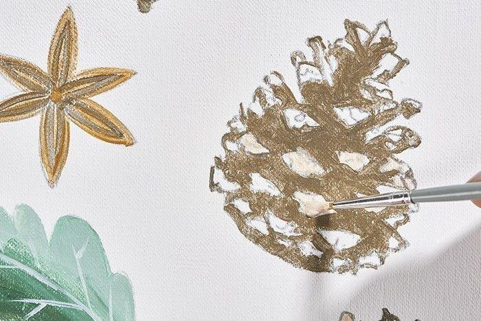 ETAPE 4/9 Pour peindre la pomme de pin, mélanger le gris et l'or pour les parties foncées, mélanger l'or et le blanc pour les zones de lumière, et apporter des touches dorées pour donner du relief au motif. Laisser sécher tous les éléments peints et les découper.