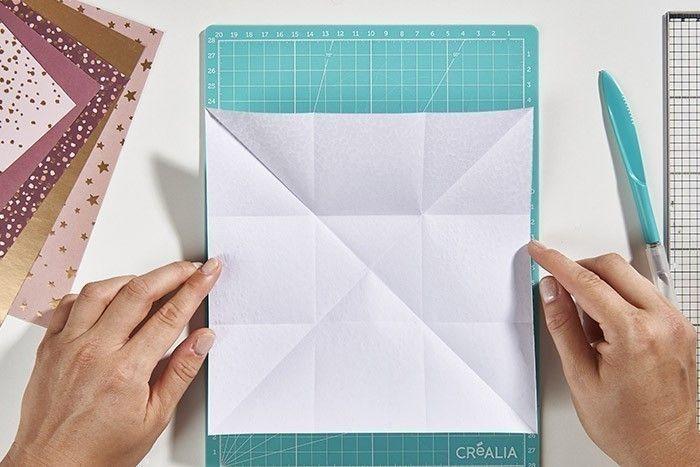 ETAPE 1/8 Pour créer une pochette origami, couper un carré de 21 cm dans un papier A4 de la collection. Marquer un pli à la verticale de 7 et 14 cm pour le plier en 3. Déplier puis recommencer pour marquer les plis à l'horizontale. Déplier à nouveau. Marquer un pli dans chaque diagonale du carré.