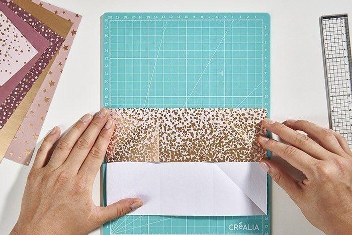 Calendrier de l'Avent Sapin Origami  - étape 1 ETAPE 1/8 Pour créer une pochette origami, couper un carré de 21 cm dans un papier A4 de la collection. Marquer un pli à la verticale de 7 et 14 cm pour le plier en 3. Déplier puis recommencer pour marquer les plis à l'horizontale. Déplier à nouveau. Marquer un pli dans chaque diagonale du carré.  Calendrier de l'Avent Sapin Origami  - étape 2 ETAPE 2/8 Rabattre le rabat de 7 cm du haut du carré. Imaginez une diagonale dans le carré central qui part de l'angle bas gauche vers l'angle haut droit.