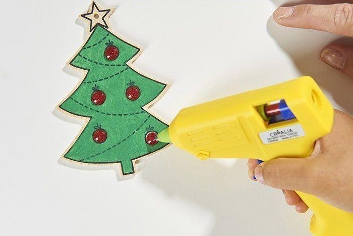 2. Insérer le bâton de colle pailleté rouge dans le pistolet à colle et aider l'enfant à déposer la colle dans les ronds pour former le relief des boules de Noël. Laisser refroidir.