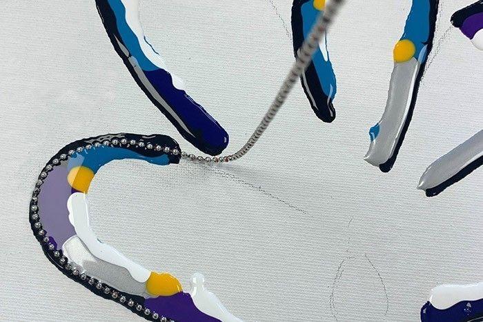 Etape 4/7 Vous pouvez compléter la deuxième ligne en rajoutant un peu de blanc et des points jaunes pour avoir des nuances plus claires. Placez délicatement la chainette entre la première et la deuxième ligne de peinture.