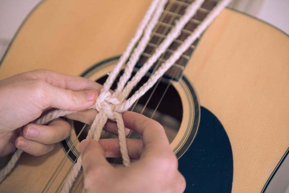 6. Attacher la guitare à une ficelle. Suspendre la guitare devant le macramé et faire coïncider le haut de la guitare avec le bas du motif. Prendre les deux brins qui se trouvent tout à gauche et les deux brins tout à droite et nouer avant la fin du manche de la guitare, avec 4 nœuds plats*. Retourner la guitare et le macramé et réaliser le même motif au dos de la guitare avec les 4 brins qui se trouvent au milieu.
