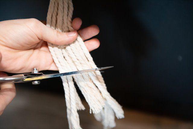 8. Rassembler toutes les ficelles sous la guitare et former un nœud. Tirer fermement un à un tous les brins. Couper pour égaliser la longueur des fils.