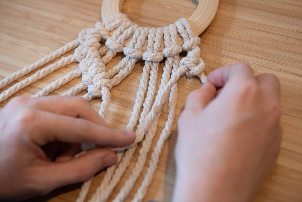 4. Réaliser une rangée de nœuds partant de la droite. Le fil porteur sera celui tout à droite. Former des nœuds avec les 11 brins. Reprendre le fil porteur de gauche qui se trouve au milieu et continuer à former vers la droite des nœuds avec les 5 brins qu'il croise. 