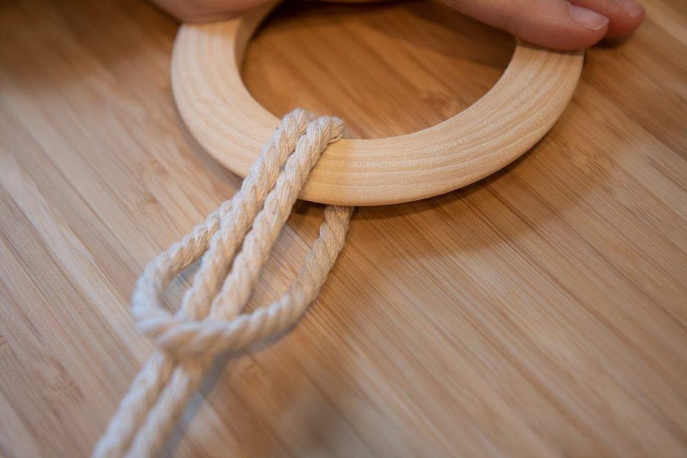 2. Fixer les 6 longueurs sur l'anneau en réalisant des nœuds d'alouette* : Plier une longueur en deux et le passer sur l'anneau en bois, boucle vers le bas. Passer les brins libres dans l'anneau et serrer pour former le nœud.