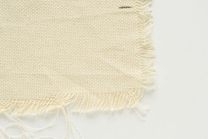 Etape 11/13 Pour réaliser des franges, tirer sur les fils de trame de la toile à puncher un rang après l'autre : ceux du bas sur 15 cm à l'horizontale et ceux de côté sur 3 cm à la verticale.