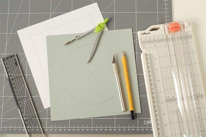 Etape 1/9 Couper un carré de papier gris aux dimensions intérieures du cadre. Marquer le centre et tracer au compas un disque de 14 cm de diamètre. Evider au cutter. Découper un cadre de mêmes dimensions sur du carton fin en laissant une marge de 2,5 cm