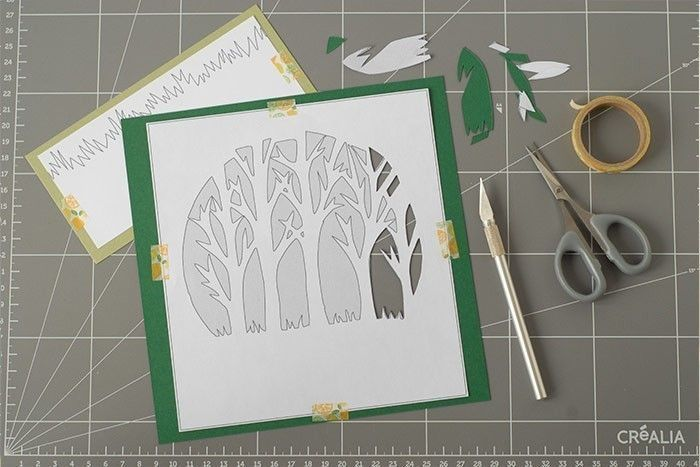 Etape 2/9 Télécharger et imprimer le gabarit des arbres et des herbes. Placer les arbres sur une feuille de papier vert foncé. Maintenir avec du ruban masking tape. Placer les herbes sur une feuille vert mousse. Evider les parties grises des arbres au cutter et aux ciseaux. Découper les herbes.