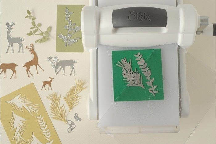 Etape 4/9 Préparer toutes les formes de découpe. Réaliser les rennes dans du papier kraft et les feuilles et branchages dans un camaïeu de verts. Suivre les instructions de la machine pour découper tous les éléments.