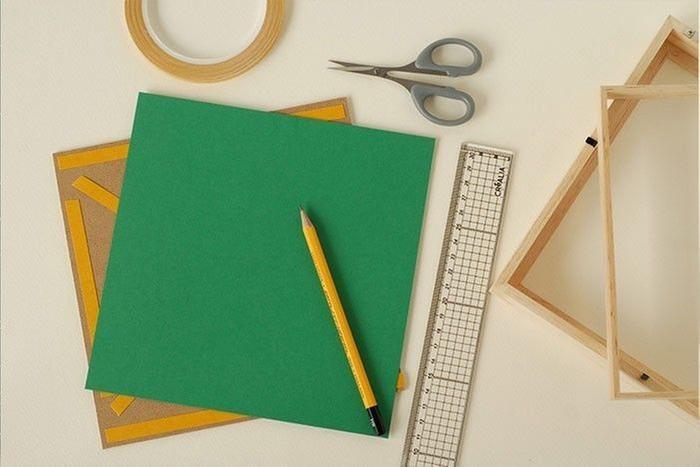 Etape 5/9 Ouvrir le cadre. Couper une feuille papier vert vif de mêmes dimensions. Sur le fond, coller du ruban adhésif double face. Ôter le film protecteur. Y fixer le papier vert vif.