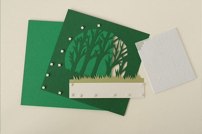 Etape 6/9 Au dos de la découpe des arbres et des herbes, coller des carrés de mousse double face. Ôter les films protecteurs. Fixer les arbres centrés sur le fond vert.