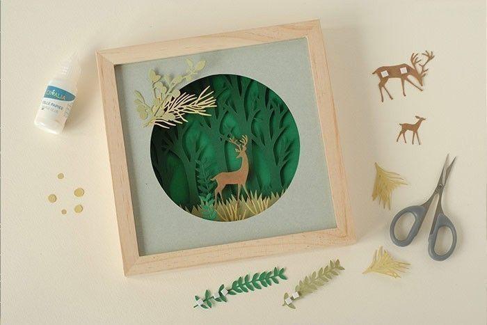 Etape 8/9 Fermer le cadre. Placer tous les feuillages et les herbes dans la composition en les maintenant avec des carrés de mousse double face. Fixer les rennes. Ajouter les feuillages au bord du cercle. Coller et ajouter les baies.