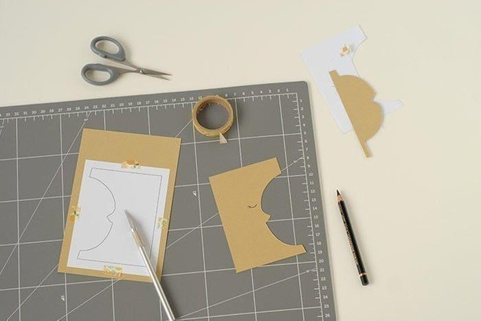 Etape 2/14 - Carte lune Télécharger et imprimer le gabarit de la lune. Placer au dos d'une feuille de papier or mat. Fixer avec du masking tape. Découper les contours. Dessiner l'œil.