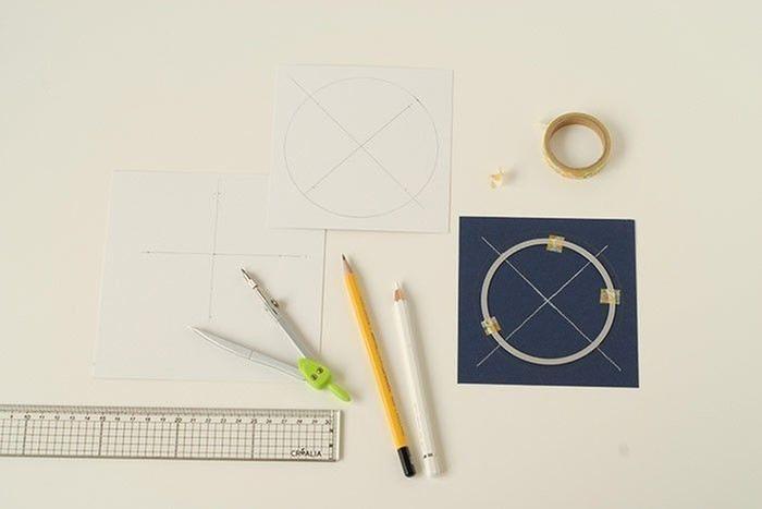 Etape 3/14 - Carte lune Au dos des carrés bleu marine et or brillant, tracer les diagonales. Reporter les mesures de la forme de découpe ronde. Ajouter 1 cm de bord au carré or brillant et 0,5 cm au carré bleu marine. Positionner la forme de découpe et maintenir avec du Masking tape.