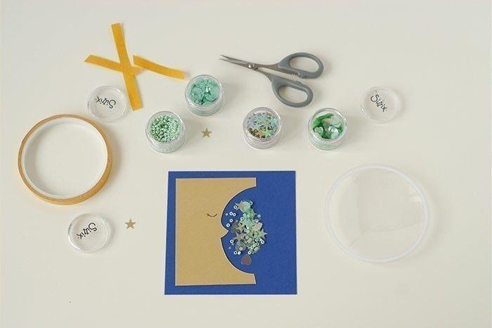 Etape 6/14 - Carte lune Coller la lune sur le fond bleu indigo. Déposer une pincée de paillettes et de perles.