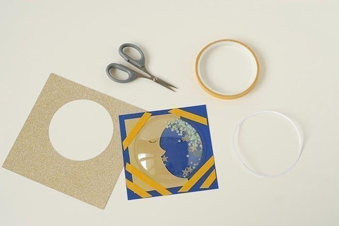 Etape 7/14 - Carte lune Ôter le film protecteur du dôme et coller sur la lune. Fixer l'ensemble sous la carte or pailleté.