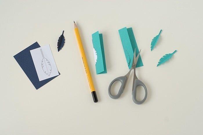 Etape 8/14 - Carte lune Télécharger et imprimer le gabarit des plumes. Découper aux ciseaux. Plier en deux. Placer sur une chute de papier bleu lagon pliée en deux. Tracer le contour au crayon. Découper. Préparer 1 plume bleu marine et 2 plumes lagon.