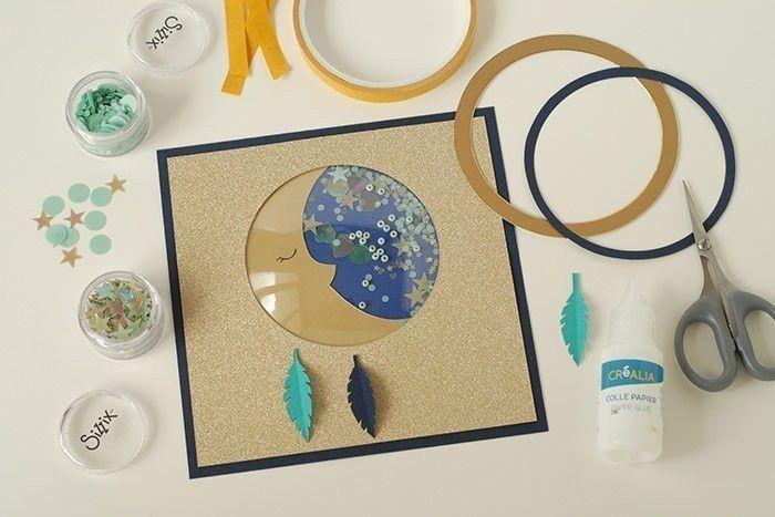 Etape 9/14 - Carte lune Coller la carte lune sur la carte bleu marine. Ajouter les 3 plumes, les anneaux or et bleu marine. Prendre des paillettes confettis et étoiles et les coller sur la carte.