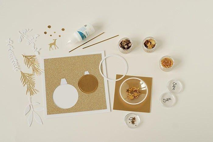 Etape 12/14 - Variante carte de vœux Remplir le dôme de paillettes et coller sur du papier or brillant. Coller sous la carte. Découper les attaches des boules de noël et de fines bandes pour les fils.