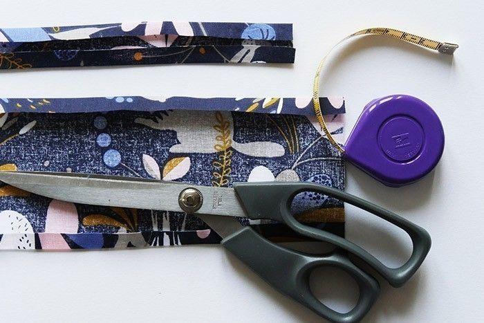 ETAPE 1/11 Coupez dans le tissu à motifs deux bandes de 4 x 50 cm et 10 x 50 cm. A l'aide d'un fer à repasser, faites un repli de 1 cm en haut et en bas de chaque bande.