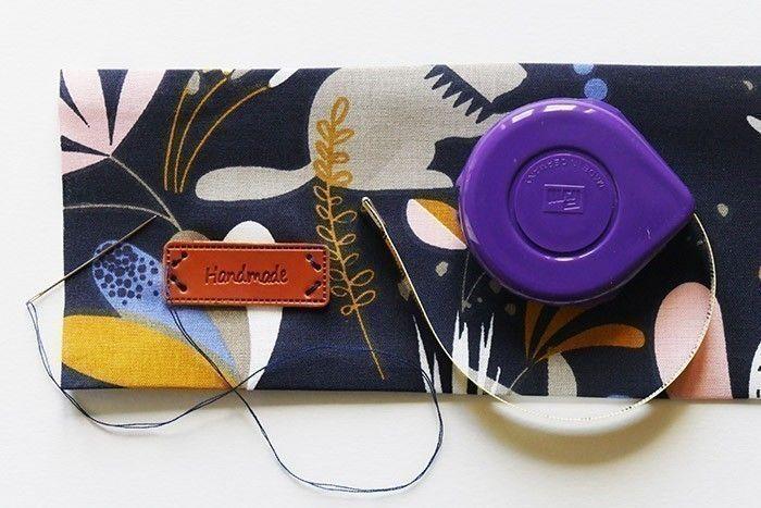 ETAPE 2/11 Avec du fil et une aiguille, cousez à la main l'étiquette « Handmade » en bas à gauche de la bande de tissu la plus large. Placez-la à 3 cm du bord gauche du tissu et à 2 cm de la pliure en bas du tissu. Faites quelques points bien serrés et arrêtez le fil sur l'envers du tissu.