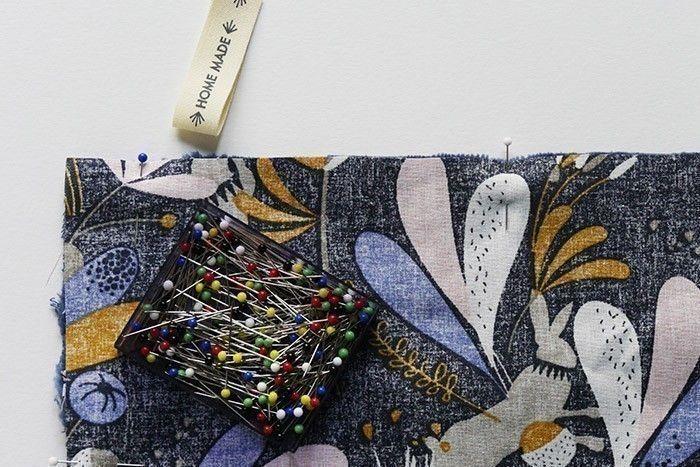 ETAPE 5/11 Coupez un rectangle de 50 x 65 cm dans le tissu à motifs. Placez-le endroit contre endroit avec l'éponge. Préparez l'étiquette qui servira d'accroche : coupez un morceau de ruban incluant la mention « Home Made » deux fois et repliez-le sur lui-même. Glissez-le entre les deux épaisseurs, pliure vers l'intérieur, à 3 cm du bord haut gauche.