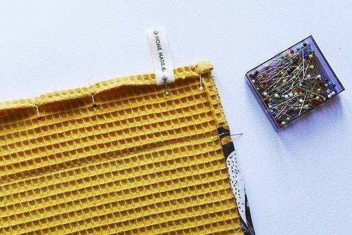 ETAPE 8/11 Au lieu de doubler le torchon, faites un repli de 1 cm + 1 cm tout autour et surpiquez à 0,8 cm. Placez le ruban qui servira d'accroche en le glissant dans le repli du tissu nid d'abeille, à quelques centimètres du coin supérieur droit sur l'envers du torchon.