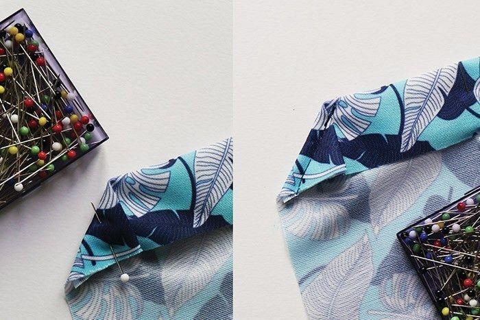 ETAPE 1/9 Coupez dans le tissu PUL un rectangle de 35 x 52 cm. Ce rectangle sera plié en deux, la pliure créant un des deux côtés du sac. Sur une des longueurs créant le haut du sac, préparez la coulisse. Faites un premier pli à 3 cm et épinglez-le. Puis, repliez les deux coins aux extrémités, toujours sur 3 cm. Surpiquez cet angle à 3 mm de la pliure.