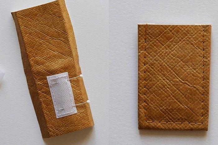 ETAPE 1/8 Commencez par préparer la languette. Coupez dans le tissu tyvek effet cuir un rectangle de 6 x 12 cm. A l'aide d'un fer à repasser, marquez un pli de part et d'autre de la longueur à 1 cm. Placez un morceau de scratch de 4 cm bien centré à partir du milieu de la languette et surpiquez-le tout autour à 2 mm. Repliez la languette en deux et surpiquez-la à 3 mm.