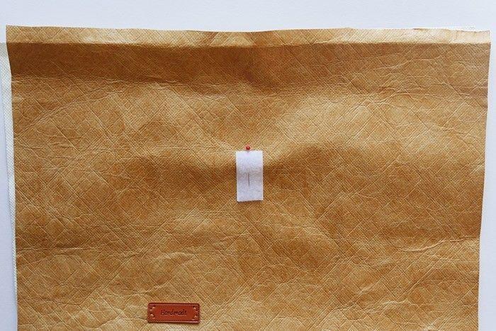 ETAPE 2/8 Coupez dans le tissu tyvek un rectangle de 35 x 65 cm. A l'aide d'un fer à repasser, marquez un pli à 1 cm au bord de chaque largeur. Placez et cousez à la main l'étiquette « Handmade » à 21 cm du bord haut et à 10 cm du côté gauche. Placez l'autre partie du scratch à 9,5 cm du bord haut et à 17,5 cm du côté droit et piquez tout autour à 2 mm.