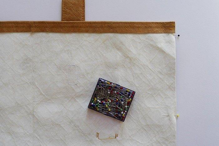 ETAPE 3/8 Placez la languette du côté opposé à l'étiquette et au scratch, bien centrée. Surpiquez la largeur à deux reprises, à 3 mm et à 1 cm du bord, en piquant par-dessus la languette pour la fixer. Surpiquez de même l'autre largeur qui ne comporte pas de languette. Repliez en deux le rectangle de tissu tyvek, endroit contre endroit, et épinglez les côtés.