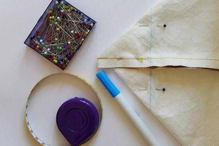 ETAPE 5/8 Pour créer l'épaisseur du lunch bag, aplatissez les coins inférieurs et mesurez une épaisseur de 12 cm. Tracez une ligne de repère perpendiculaire à la couture du côté et piquez sur cette ligne. Recoupez l'excédent de tissu en forme de triangle pour alléger la structure du lunch bag. Répétez cette étape au niveau de l'autre coin inférieur.
