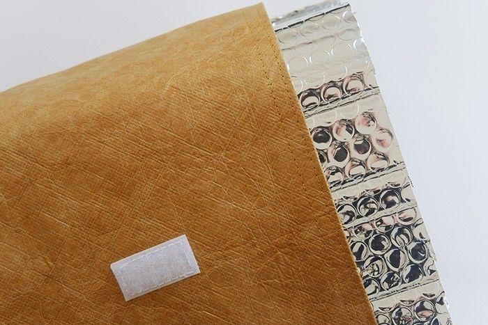 ETAPE 8/8 Glissez la structure en tissu isolant thermique dans la housse en tissu tyvek. Comme celui-ci passe à la machine, il suffira d'ôter la structure isolante avant chaque lavage de votre lunch bag (30°). Repliez l'épaisseur du lunch bag vers l'intérieur avant de rabattre le haut et de le fermer grâce à la languette.