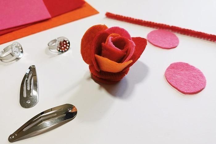 ETAPE 4/8 Poursuivre le relief des pétales avec d'autres ronds de feutrine collés autour du cœur de la fleur, au niveau de la base. Enrouler et coller un fil chenille pour décorer la base de la fleur puis coller la fleur sur une barrette ou un support de bague à l'aide d'un pistolet à colle (manipulation par un adulte).