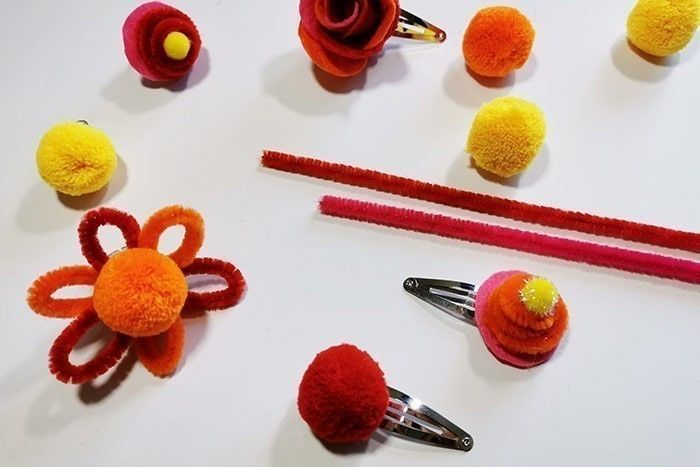 ETAPE 5/8 Créez des variantes de bagues et barrettes en collant un gros pompon, en faisant une fleur en fils chenille avec au centre un gros pompon ou en superposant à un rond de feutrine un fil chenille enroulé en spirale avec un pompon collé au centre.
