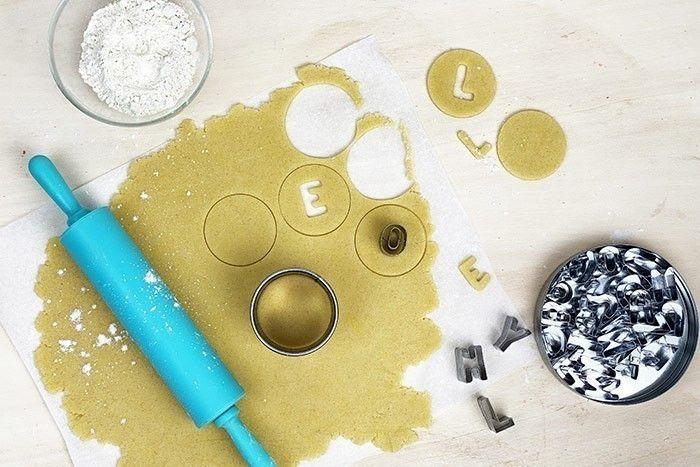 ETAPE 3/7 Sur du papier cuisson étaler la pâte sur 0,5cm d'épaisseur,  fariner légèrement le rouleau . Découper dans la pâte des disques et découper les lettres dans 1 disque sur 2 : un biscuit lettre, un biscuit simple.  Dans un four chaud cuire 10-12min à 180° jusqu'à coloration et laisser refroidir. Astuce pour un effet brillant, avec un pinceau étaler un peu de jaune d'œuf sur les biscuits avant cuisson.