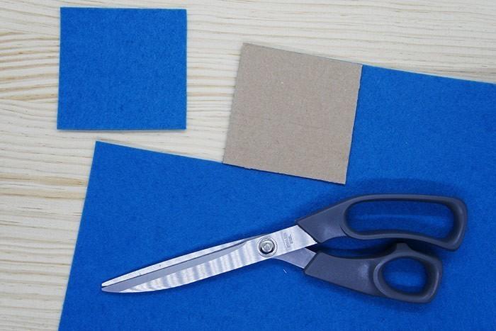 ETAPE 2/9 Coupez 20 carrés de feutrine pour préparer le dos des cartes à l'aide du gabarit carré de 8 x 8 cm. Conseil : Soyez bien précis pour que les carrés soient réguliers et parfaitement identiques.