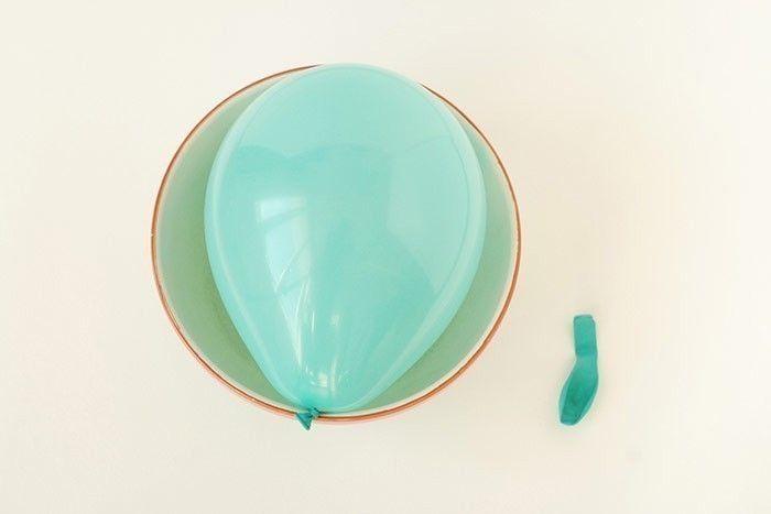 ETAPE 1/8 Gonfler un ballon, faire un nœud et le placer dans un saladier pour le maintenir. Placer sur un plan de travail protégé ou sur une toile cirée et protégez-vous avec un tablier.